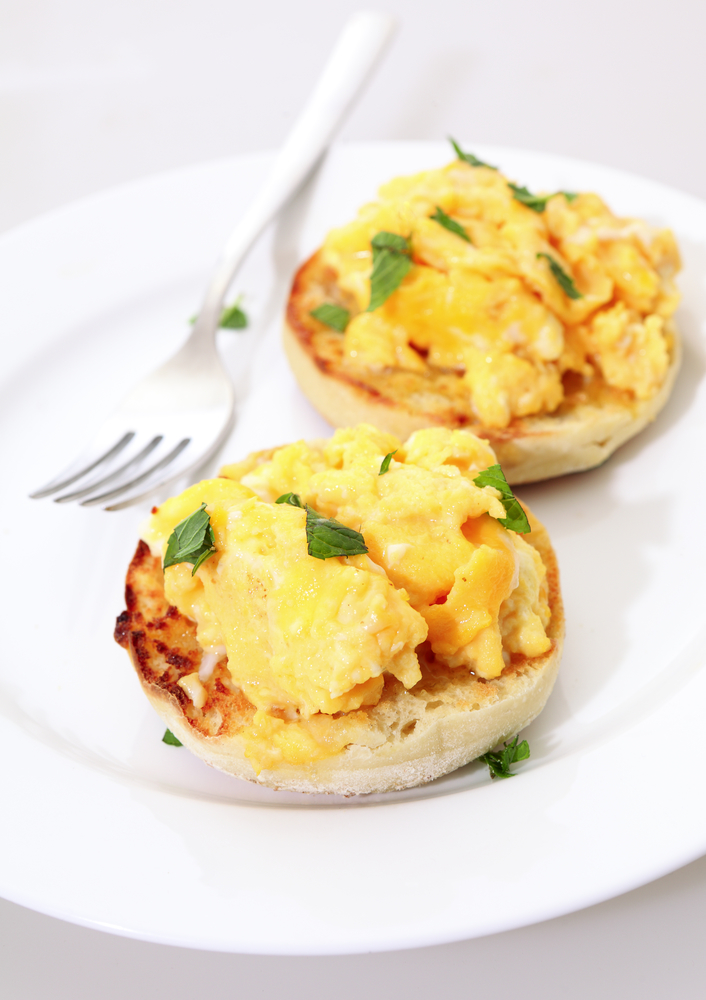 Toasted muffins topped with scrambled egg garnished with chopped mint on a plate with a fork.